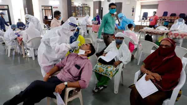 Healthcare workers wearing personal protective equipment (PPE) kits collect swab samples (Photo: ANI)