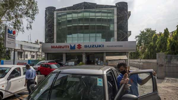 A worker cleans a vehicle outside a dealership for Maruti Suzuki India