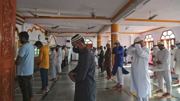 Indian Muslims wearing face masks and maintaining social distance offer Eid al-Adha prayers at a masjid (AP)