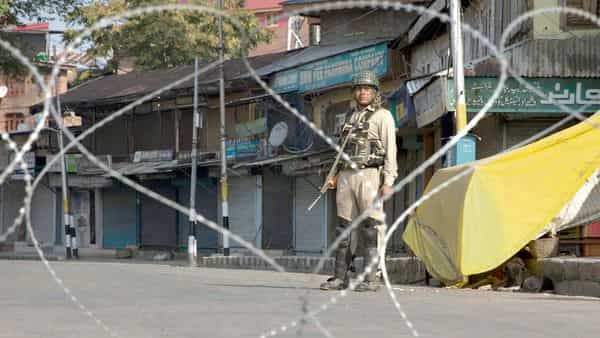 Paramilitary forces standing guard near a temporary checkpoint in Srinagar on 23 August 2019. (Photo: AP)