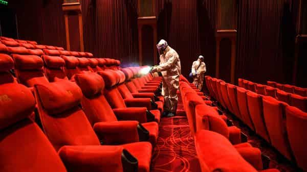 PVR Cinemas employees wearing Personal Protective Equipment (PPE) suits sanitise a cinema hall