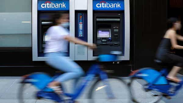 Cyclists wearing protective masks ride past a Citigroup Inc. Citibank bank branch in New York. (Bloomberg)