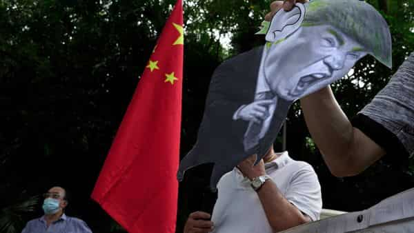 FILE - In this Aug. 8, 2020, file photo, pro-China supporters display a picture of U.S. President Donald Trump during a protest against the U.S. sanctions outside the U.S. Consulate in Hong Kong. China has announced Monday, Aug. 10, 2020, unspecified sanctions against 11 U.S. politicians and heads of organizations promoting democratic causes, including Senators Marco Rubio and Ted Cruz, who have already been singled out by Beijing. (AP Photo/Vincent Yu, File) (AP)