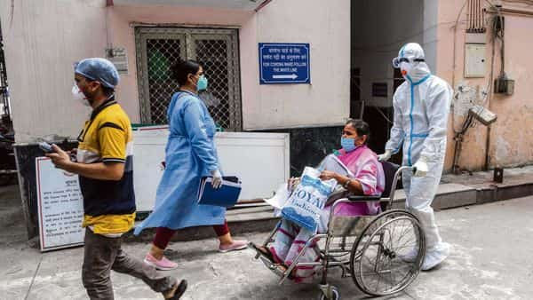 A health worker in safety gear shifts a patient in a wheelchair to a covid-19 ward at a hospital in New Delhi on Wednesday. (AFP)