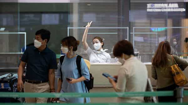 An employee wearing a protective mask and face shield calls for passengers
