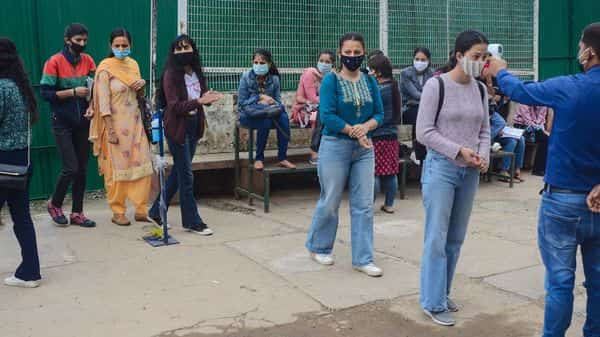 Shimla: A worker conducts thermal screening of students as they enter RKMV college to appear in their exams, in Shimla, Monday, Aug. 17, 2020.  (PTI)