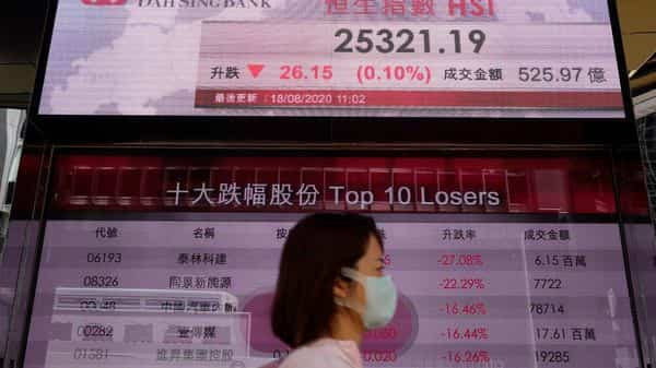 A woman wearing a face mask walks past a bank's electronic board showing the Hong Kong share index at Hong Kong Stock Exchange on Tuesday. (AP)