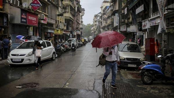 A pedestrian carrying an umbrella walks along a street in Mumbai. BSE Sensex slumped around 400 points today