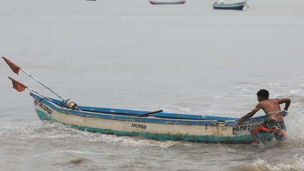 A fisherman pulls his boat out of sea to anchor it  (REUTERS)