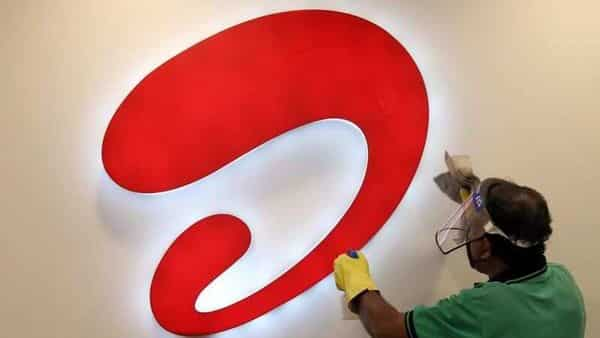 A man wearing a protective face shield cleans a Bharti Airtel logo inside its store,  (REUTERS)