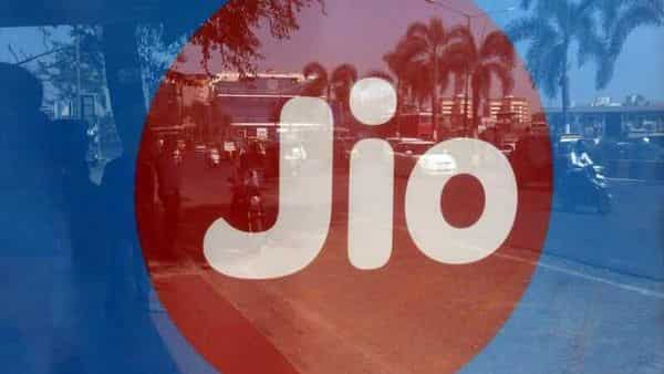 FILE PHOTO: Commuters are reflected on an advertisement of Reliance Industries' Jio telecoms unit, at a bus stop in Mumbai, India, February 21, 2017. REUTERS/Shailesh Andrade/File Photo (REUTERS)