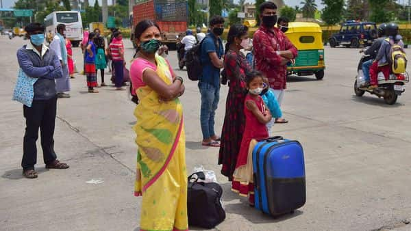 People wait for means of transportation as they leave the city after authorities announced one week lockdown due to surge in COVID-19 cases, in Bengaluru (PTI)