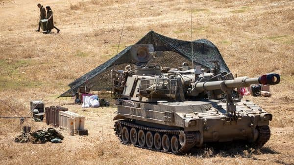 Israeli soldiers carry a box next to their mobile artillery piece near the border with Lebanon, northern Israel, Wednesday, Aug. 26, 2020. The Israeli military said attack helicopters have struck observation posts of the militant Hezbollah group along the Lebanon border after shots were fired at Israeli troops.  (AP)