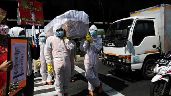 Government workers in Jakarta wearing protective suits carry a mock-up of a coffin to warn people about coronavirus