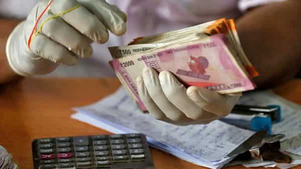 A trader wearing protective hand gloves counts Indian currency notes (Reuters)