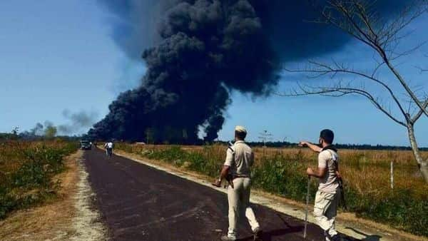 Policemen try to get people off the road following an explosion at an oil well in Baghjan, Assam. India may be climbing the global rankings on the ease of doing business, but its environmental protection record remains dismal. ( Photo: AFP)