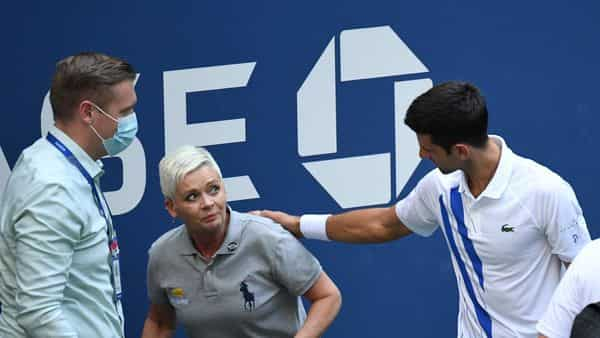 Novak Djokovic of Serbia and a tournament official tend to a linesperson who was struck with a ball by Djokovic against Pablo Carreno Busta of Spain (not pictured) on day seven of the 2020 U.S. Open tennis tournament at USTA Billie Jean King National Tennis Center. (USA TODAY Sports)