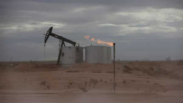 Dust blows around a crude oil pump jack and flare burning excess gas at a drill pad in the Permian Basin in Loving County, Texas, U.S. (REUTERS)