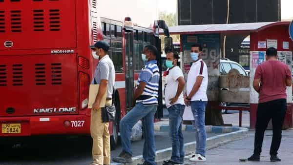 People wearing protective masks wait to board a bus at a station in Kuwait City. (AFP)