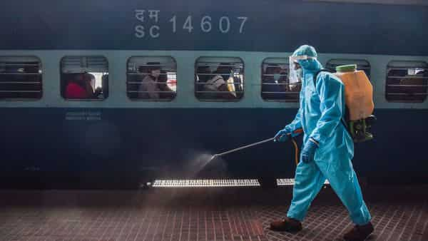 A worker sprays disinfectant on a platform before the departure   (PTI)