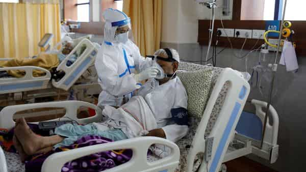 A medical worker takes care of a patient suffering from the coronavirus disease (COVID-19), at the Intensive Care Unit (ICU) of the Yatharth Hospital in Noida, on the outskirts of New Delhi. (REUTERS)
