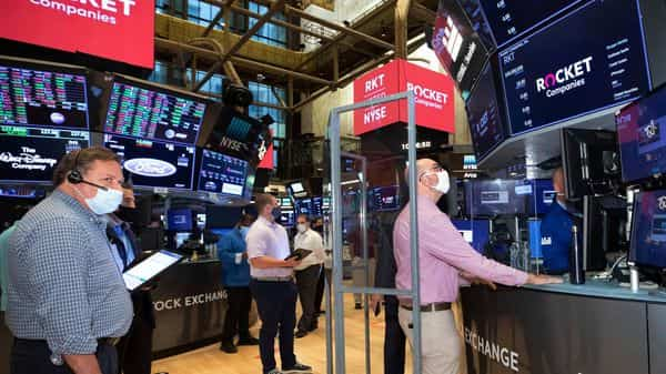 In this image provided by the NYSE, traders use social distancing as specialist Peter Giacchi, right, works behind a protective barrier during the Rocket Companies IPO, on the floor of the New York Stock Exchange, Thursday Aug. 6, 2020. Stocks are drifting on Wall Street Thursday after a report showed the pace of layoffs across the country is slowing, though it remains incredibly high. (Nicole Pereira/NYSE via AP) (AP)