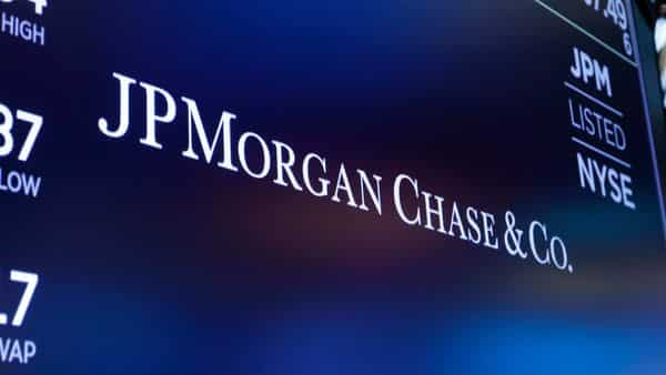 FILE - In this Aug. 16, 2019, file photo, the logo for JPMorgan Chase & Co. appears above a trading post on the floor of the New York Stock Exchange in New York. A number of JPMorgan Chase traders have been sent home after employees tested positive for COVID-19, less than a week into the bank's push to start bringing its workers back into the office. A bank spokesman said Tuesday, Sept. 25, 2020, that JPMorgan Chase has been managing individual positive cases over the last few months. (AP Photo/Richard Drew, File) (AP)