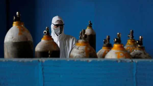 A medical worker stands next to an oxygen cylinder at the Yatharth Hospital in Noida, on the outskirts of New Delhi, (REUTERS)