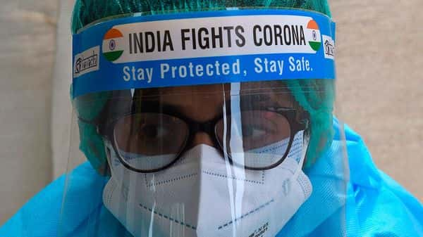 A health worker wearing a face shield reading 'India Fights Corona' waits for patients at a temporary Covid-19  testing centre settled by the Ahmedabad Municipal Corporation. (AFP)
