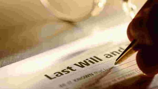 A close up of a man signing his last will and testament (istockphoto)