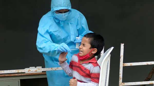 A child reacts as a health worker collects a swab sample for a Covid-19 test at a primary health centre in Hyderabad (AFP)