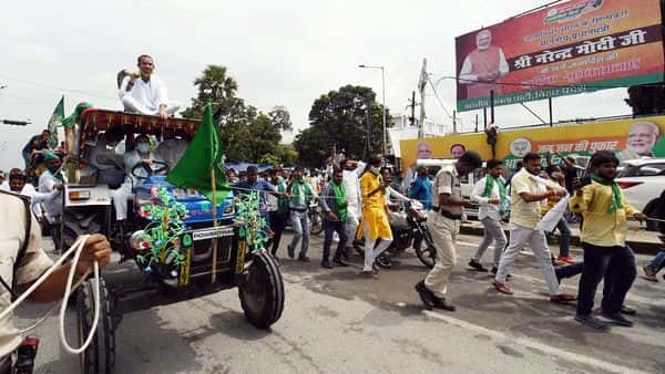 RJD leaders Tejaswi Yadav with Tej Pratap ride a tractor during the Bharat Bandh call against the Farm Bills passed by Parliament in Patna