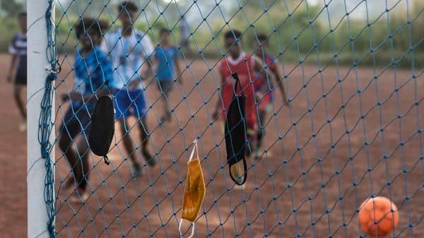 Children hang their face masks in the nets and play a game of soccer during the COVID-19 pandemic in Kochi, Kerala, India (AP)