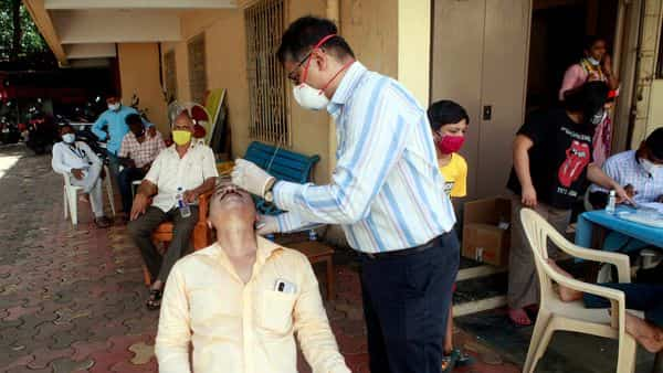 BMC Medical staff collects swab sample while conducting rapid antigen tests at Shivaji Park, Under BMC's 'Mission Zero' in Mumbai on Monday. (ANI Photo)