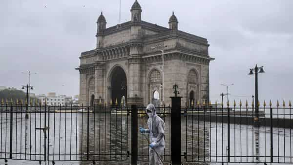 A worker wearing a protective mask sweeps the ground at a deserted Gateway of India in Mumbai. (Bloomberg)