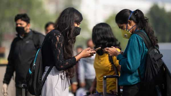Women wearing facemasks as a preventive measure against the COVID-19 coronavirus use their mobile phones outside a metro station in New Delhi (AFP)