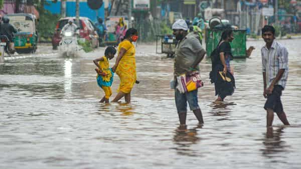 People wade through a waterlogged road during heavy rains, due to a deep depression in Bay of Bengal, in Vijayawada. (PTI)