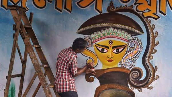 An artist paints a graffiti of Hindu goddess Durga on a wall, part of a campaign ahead of upcoming Durga Puja festival, in Kolkata. (PTI )