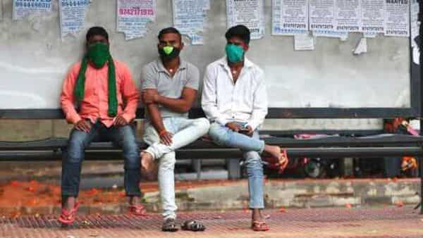 Indians wearing face masks as a precaution against the coronavirus wait at a bus stop in Bengaluru, India, Sunday, Oct. 11, 2020. India's confirmed coronavirus toll crossed 7 million on Sunday with a number of new cases dipping in recent weeks, even as health experts warn of mask and distancing fatigue setting in. (AP Photo/Aijaz Rahi) (AP)