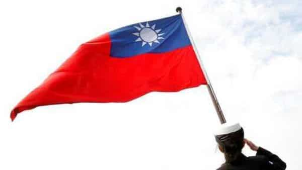 File photo, a Taiwanese military officer salutes Taiwan's flag (AP)