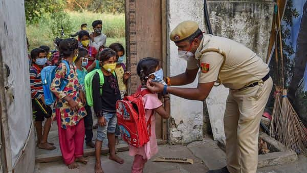 New Delhi: Delhi Police constable Than Singh, posted at Lal Qila Chowki of Kotwali police station area, adjusts the mask of a child as they arrive to attend classes at Red Fort parking,  (PTI)