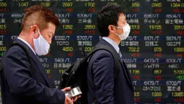People walk by an electronic stock board of a securities firm in Tokyo. (AP)