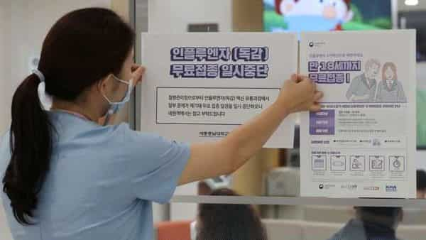 A health worker attaches a notice for suspension of influenza vaccination programs on an entrance of a hospital in Sejong, South Korea