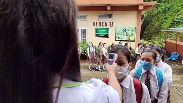 A teacher check temperature of Class 12 students with a thermal screen during the Mizoram Board of School Education (ANI)