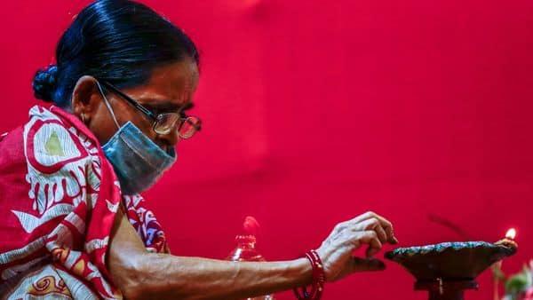 An elderly woman wearing a face mask lights an oil lamp inside a makeshift worship venue during Durga Puja in Kolkata (AP)