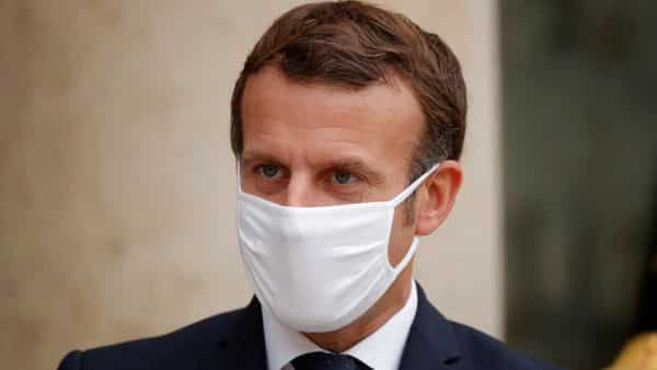 French President Emmanuel Macron, wearing a protective face mask, stands outside the Elysee Palace in Paris, France, October 28, 2020.  (REUTERS)