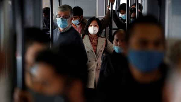 Passengers wearing protective face masks travel on a tram. (REUTERS)