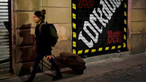 A woman wearing a face mask pushes her suitcase on a street, after Catalonia's government imposed new restrictions in an effort to control the spread of the coronavirus disease (COVID-19), in Barcelona, Spain October 29, 2020. REUTERS/Nacho Doce (REUTERS)