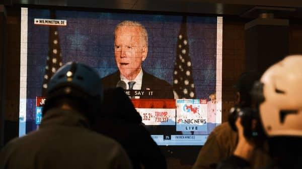 People watch Joe Biden give a speech  (AFP)