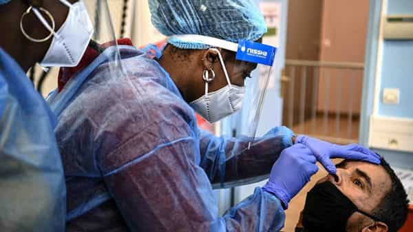 A medical worker holds a swab as she performs an antigen test for Covid-19 on a man at a screening centre in Saint-Denis, north of Paris, on November 4, 2020. (AFP)